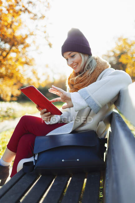 Junge Frau nutzt digitales Tablet auf herbstlicher Parkbank — Stockfoto