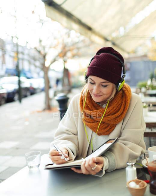 Молодая женщина в наушниках пишет в журнале в осеннем кафе на тротуаре — стоковое фото