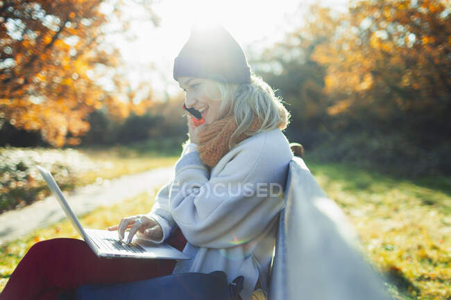 Young woman using laptop and talking on smart phone on sunny autumn park bench — Stock Photo