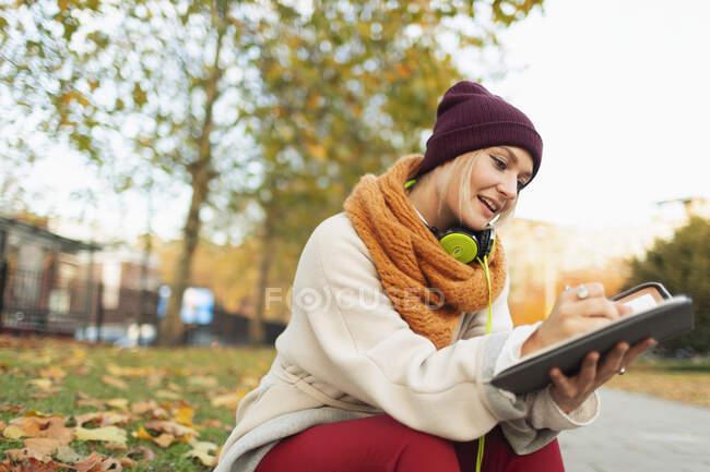 Молода жінка пише в журналі осіннього парку. — стокове фото
