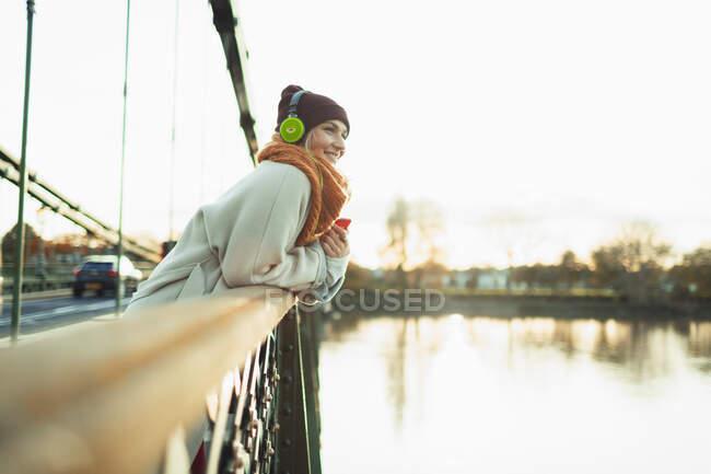 Carefree woman listening to music with headphones on autumn bridge — Stock Photo