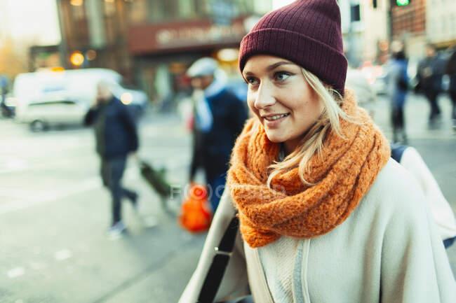 Молодая женщина в шапочке и шарфе на городской улице — стоковое фото