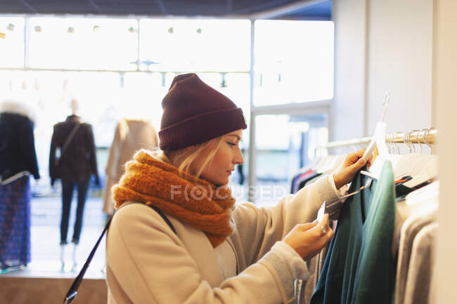 Young woman shopping in clothing store, checking price tag — Stock Photo