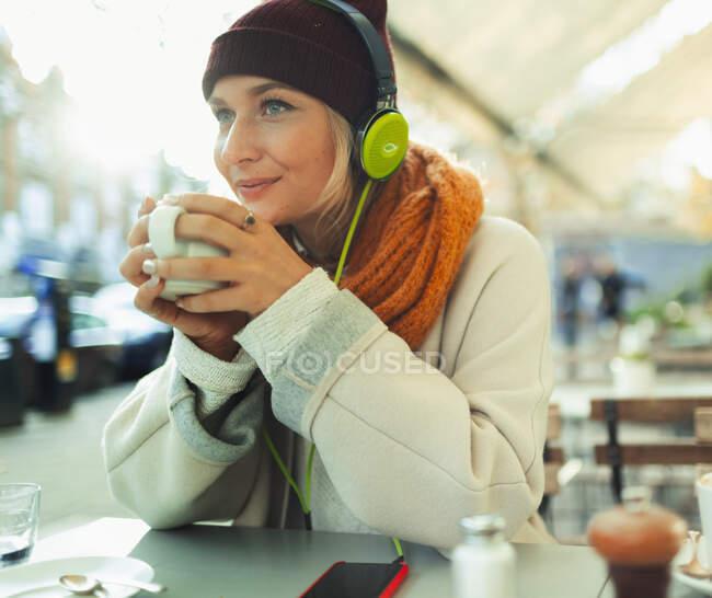 Junge Frau mit Kopfhörern hört Musik und trinkt Kaffee im Straßencafé — Stockfoto