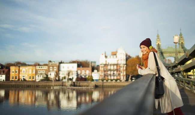 Mujer joven con gorra de siembra y bufanda en el puente urbano de otoño - foto de stock