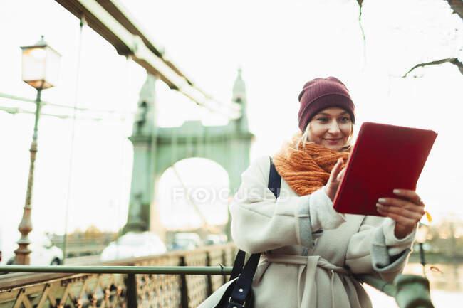 Mujer joven con gorra de siembra y bufanda usando tableta digital en puente urbano. - foto de stock