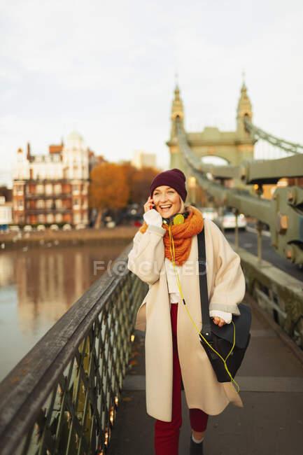 Jovem mulher em meia tampa e cachecol falando no telefone inteligente na ponte urbana — Fotografia de Stock