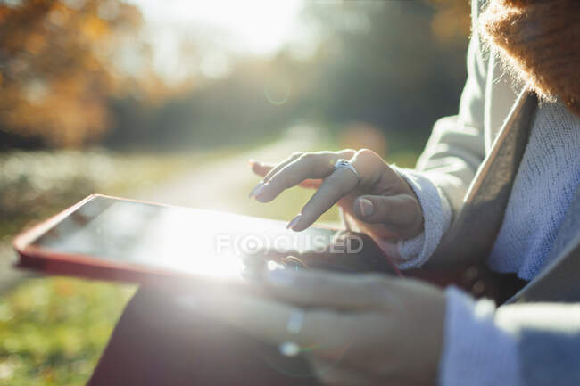 Close up woman using digital tablet in sunny autumn park — Stock Photo
