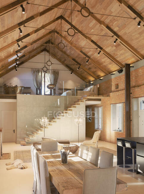 Home showcase interior dining room with wood vaulted ceiling and spiral staircase loft — Stock Photo