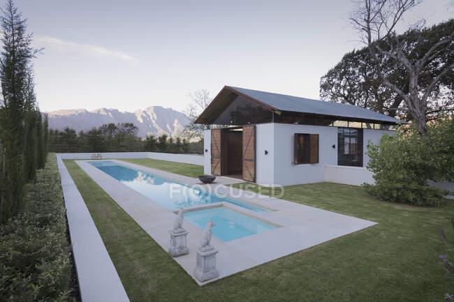 Idílico, piscina de luxo e piscina com montanhas ao fundo — Fotografia de Stock