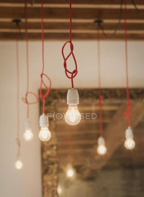 Ampoules électriques suspendues à un cordon noué — Photo de stock