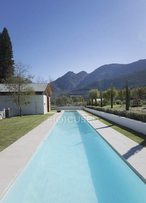 Luxury sunny lap pool with mountains in background — Stock Photo