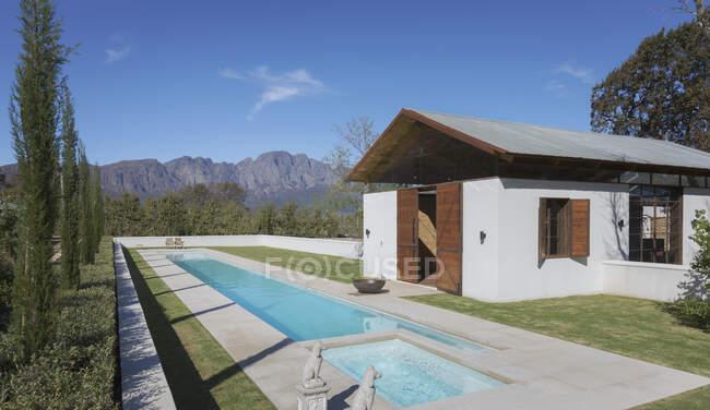 Idílico, piscina de luxo ensolarado e piscina casa com montanhas em segundo plano — Fotografia de Stock