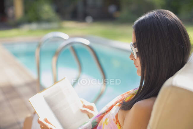 Libro de la mujer leyendo en la soleada piscina de verano - foto de stock