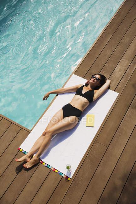 Sensual woman in black bikini sunbathing at sunny summer poolside — Stock Photo