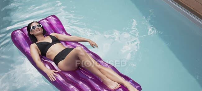 Serene woman in black bikini relaxing, laying on inflatable raft in sunny summer swimming pool — Stock Photo