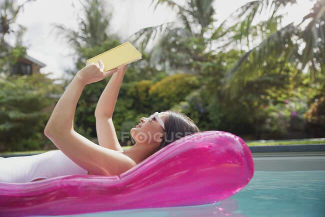 Женщина читает книгу о надувном плоту в солнечном летнем бассейне — стоковое фото