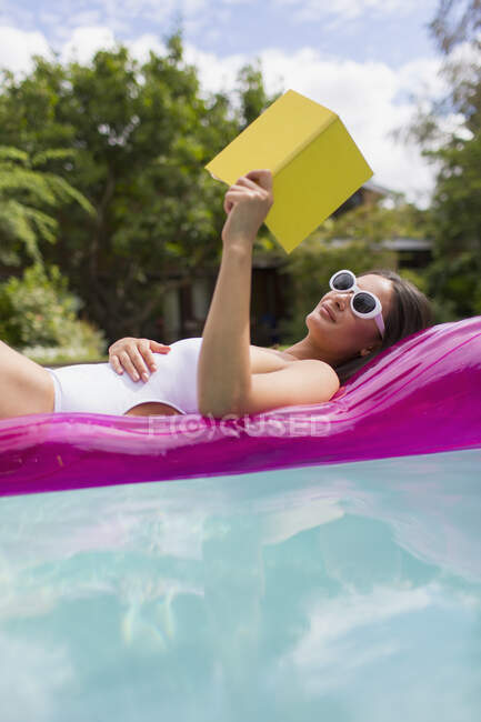 Woman relaxing, reading book on inflatable raft in summer swimming pool — Stock Photo