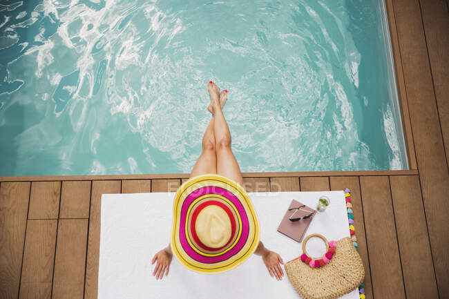 Woman in sun hat relaxing at summer poolside — Stock Photo
