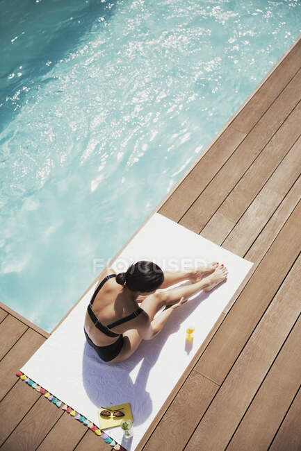 Woman applying sunscreen to legs at sunny summer poolside — Stock Photo