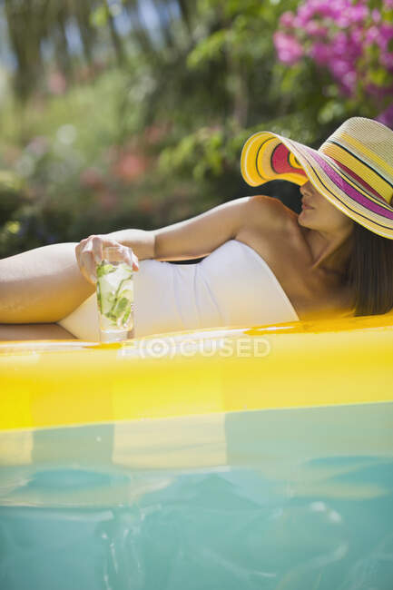 Sensual woman in bathing suit and sun hat relaxing with cocktail on inflatable raft in sunny swimming pool — Stock Photo