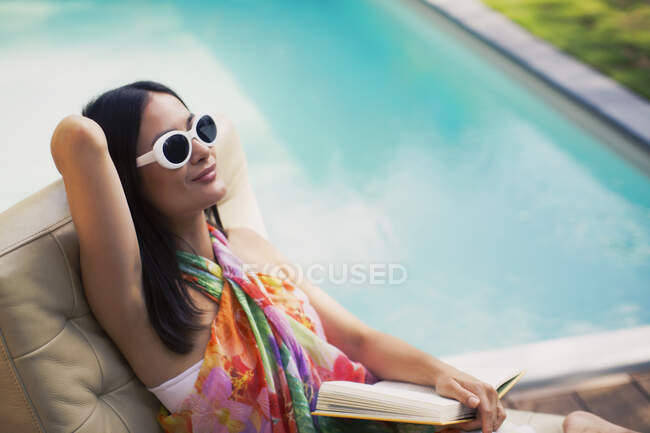 Serene woman relaxing, reading book at summer poolside - foto de stock