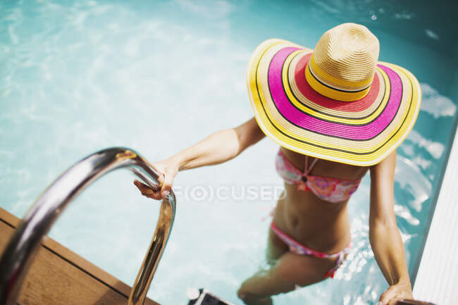 Woman in sun hat and bikini getting out of sunny summer swimming pool — Stock Photo