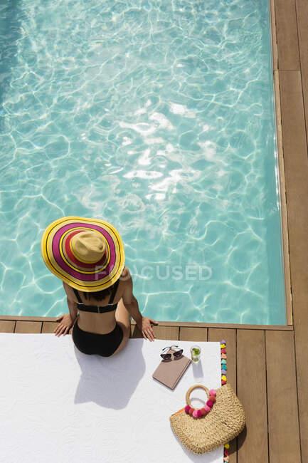 Woman in sun hat and bikini relaxing at sunny poolside — Stock Photo