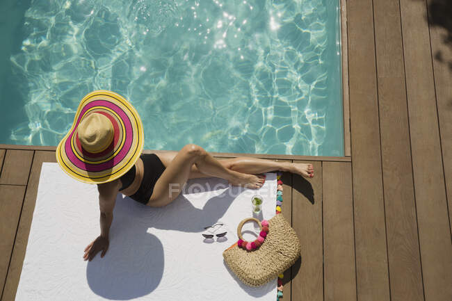 Woman in sun hat sunbathing, relaxing at sunny summer poolside — Stock Photo