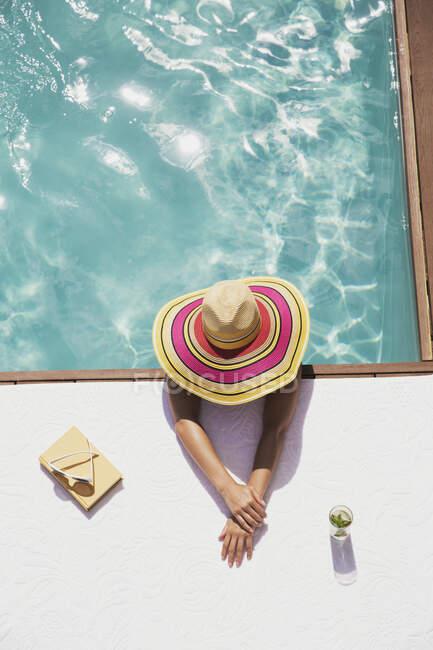 Woman in sun hat relaxing in swimming pool — Stock Photo