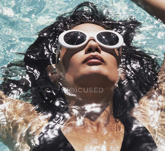 Close up serene woman in sunglasses relaxing, floating in sunny summer swimming pool — Stock Photo