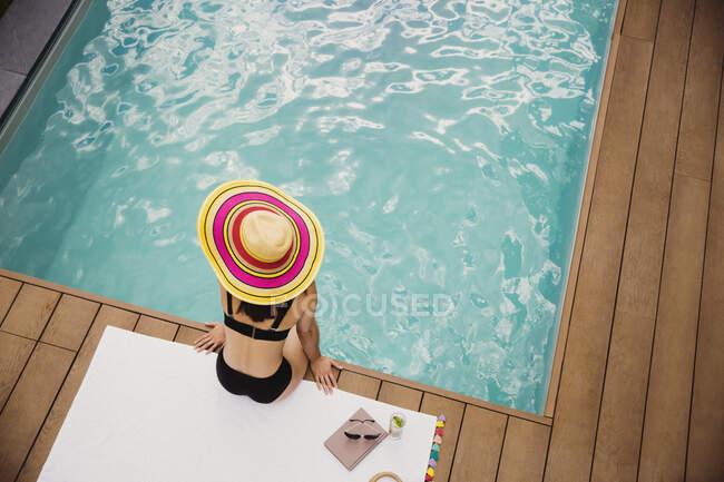 Mulher com chapéu de sol e biquíni relaxando na piscina — Fotografia de Stock