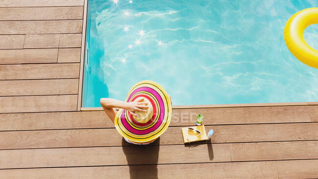 Woman in sun hat relaxing at sunny poolside — Stock Photo