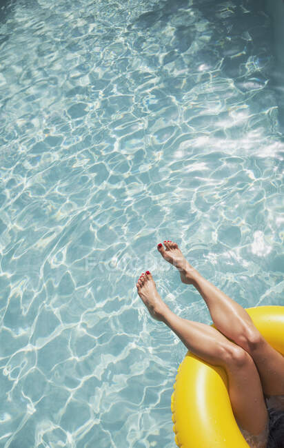 Woman with bare feet relaxing, floating in inflatable ring in sunny swimming pool — Stock Photo
