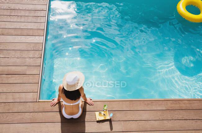 Mulher de chapéu de sol relaxante na ensolarada piscina de verão — Fotografia de Stock