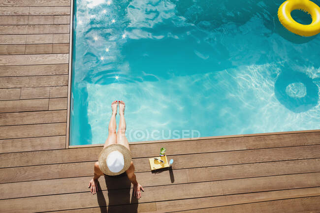 Woman in sun hat relaxing, sunbathing at sunny summer poolside — Stock Photo