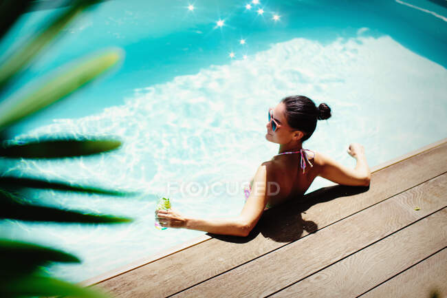 Woman relaxing with cocktail in sunny summer swimming pool — Stock Photo