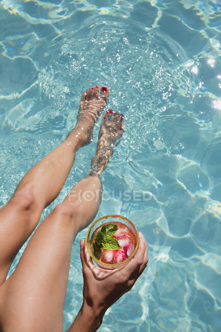 Barefoot woman with cocktail dipping bare feet in sunny summer swimming pool — Stock Photo