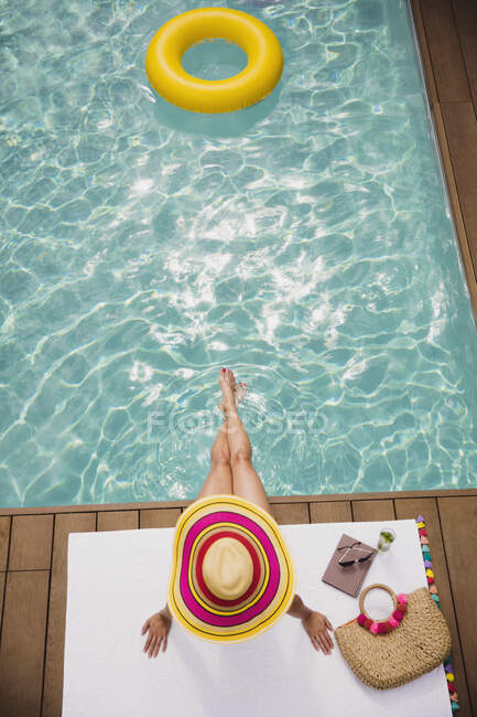 Woman in sun hat relaxing, sunbathing at summer poolside — Stock Photo