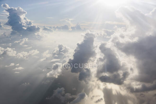 Aerial view sunbeams and fluffy white clouds in ethereal sky — Stock Photo