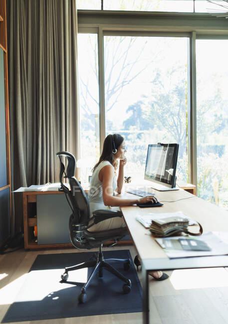 Бизнесвумен в наушниках работает за компьютером в домашнем офисе — стоковое фото