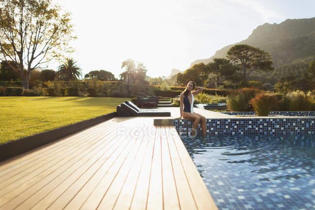Молода жінка в купальнику відпочиває в сонячному басейні розкішного плавання (Кейптаун, ПАР). — стокове фото