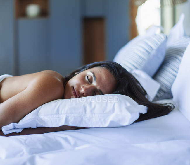 Serene young woman sleeping on pillow in bed — Stock Photo