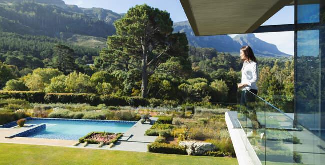 Mujer de pie en el soleado y lujoso balcón con vistas a la piscina y el paisaje, Ciudad del Cabo, Sudáfrica - foto de stock