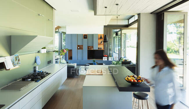 Woman walking in modern, luxury kitchen — Stock Photo