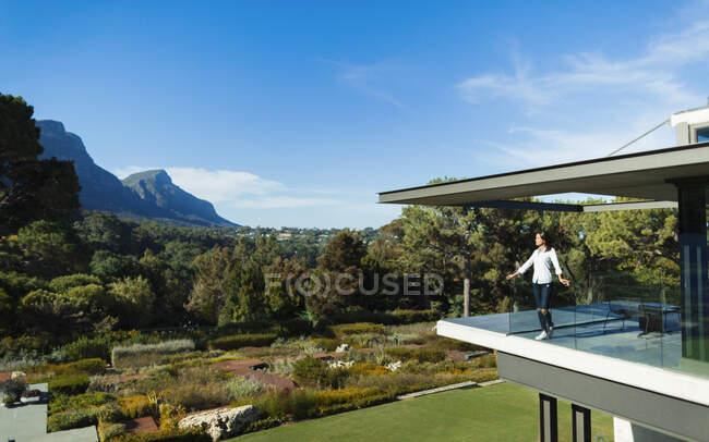 Frau auf sonnigem, modernem Luxus-Balkon mit Blick auf Garten und Berge, Kapstadt, Südafrika — Stockfoto