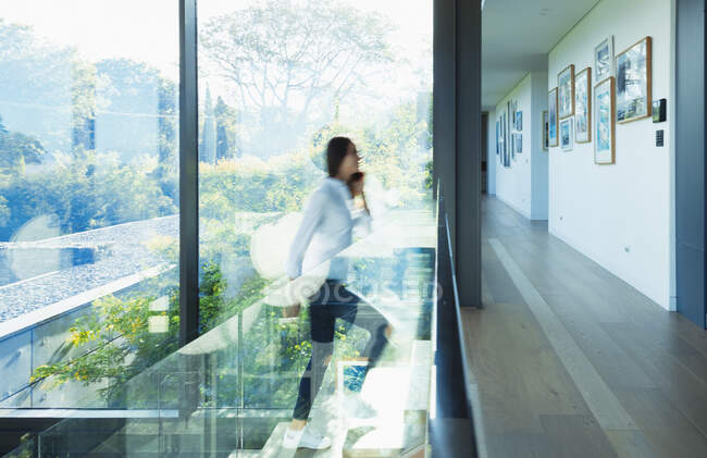 Woman ascending stairs in sunny modern, luxury home — Stock Photo