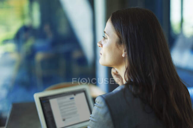 Thoughtful businesswoman working at laptop, looking away — Stock Photo