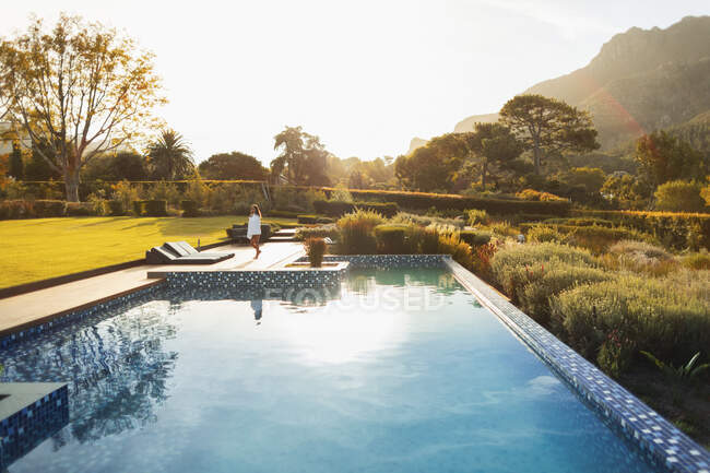 Woman walking at sunny, idyllic poolside, Cape Town, South Africa — Stock Photo