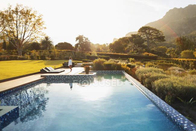 Femme marchant au soleil, idyllique au bord de la piscine, Cape Town, Afrique du Sud — Photo de stock